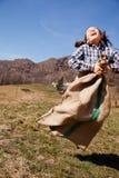 Lilla flickan hoppar i en säck av potatisar royaltyfria bilder