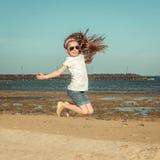 Lilla flickan hoppar på en strand Arkivbild