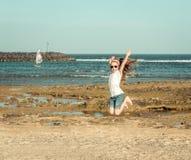 Lilla flickan hoppar på en strand Royaltyfri Fotografi