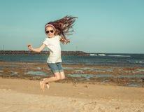 Lilla flickan hoppar på en strand Royaltyfria Foton
