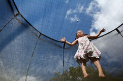 Lilla flickan hoppar på en trampolin Arkivfoto