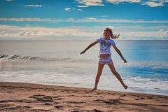 Lilla flickan hoppar på stranden royaltyfria bilder