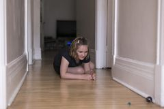 Lilla flickan huka sig ned på korridorädelträgolvet som spelar med små och stora exponeringsglasmarmor i mjuk fokus royaltyfri bild