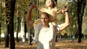 Lilla flickan i armarna av hans fader går i höst parkerar royaltyfria bilder