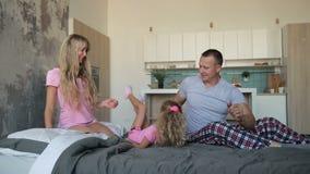 Lilla flickan, i att göra för pyjamas, slår en kullerbytta på säng stock video