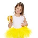 Lilla flickan i den gula kjolen som äter en banan Arkivbild