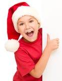 Lilla flickan i den santa hatten rymmer det tomma brädet Royaltyfria Foton