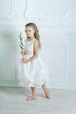 Lilla flickan i den vita klänningen och blomman poserar arkivbild