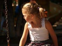 Lilla flickan i den vita t-skjortan sitter på en gunga arkivbilder