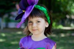 Lilla flickan i en dräkt av den violetta blomman ler Arkivfoto
