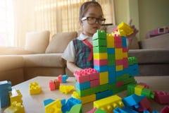 Lilla flickan i en färgrik skjorta som spelar med konstruktionsleksaken, blockerar byggande av ett torn Arkivfoto
