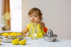 Lilla flickan i en gul klänning förbereder lemonad royaltyfria foton