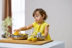 Lilla flickan i en gul klänning förbereder lemonad fotografering för bildbyråer