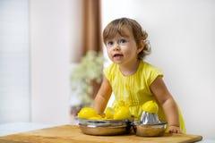 Lilla flickan i en gul klänning förbereder lemonad royaltyfri fotografi