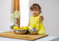 Lilla flickan i en gul klänning förbereder lemonad royaltyfri bild