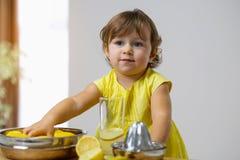 Lilla flickan i en gul klänning förbereder lemonad royaltyfri foto