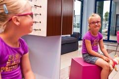 Lilla flickan i en optiker shoppar Royaltyfri Foto