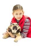 Lilla flickan i en röd väst kramar hans hund Arkivbilder