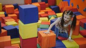 Lilla flickan i en trampolinmitt bygger ett torn av färgglade mjuka kuber stock video