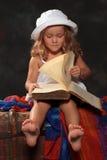 Lilla flickan i en vit hatt bläddrar igenom en stor bok på ett mörker Royaltyfri Bild