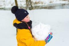 Lilla flickan i ett gult omslag och en vinterhatt bär ett stort kastar snöboll flickan gör en snögubbe royaltyfri bild