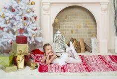 Lilla flickan i felik pixidräktklänning poserar bredvid Chren Arkivbild