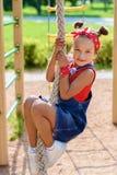 Lilla flickan i grov bomullstvilloveraller och en röd T-tröja och halsduk spelar och har gyckel på lekplatsen arkivbilder