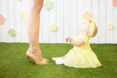 Lilla flickan i guling ser upp på mamman royaltyfri bild