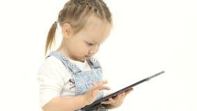 Lilla flickan i hennes händer är hållande aipad Vit bakgrund lager videofilmer