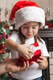 Lilla flickan i jultomtenhatt öppnar den röda gåvaasken för jul i fett Arkivfoton