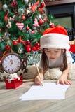 Lilla flickan i jultomtenhatt skrivar brevet till jultomten Arkivfoton