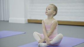 Lilla flickan i kjol sitter på mattt och väntar på början av grupper lager videofilmer