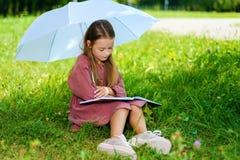 Lilla flickan i klänningläsebok parkerar in royaltyfri fotografi