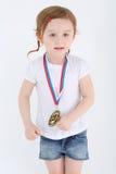 Lilla flickan i kortslutningar med medaljen på hennes bröstkorg står och ser Royaltyfri Fotografi