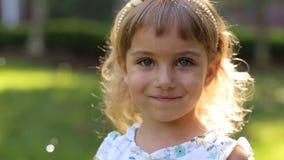 Lilla flickan i olik ögonfärg i parkerar, henne spelar med såpbubblor stock video