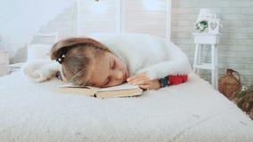 Lilla flickan i pyjamas, avverkar sovande, medan läsa en bok som är dold med den vita woolen filten lager videofilmer