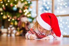 Lilla flickan i röd julhatt skrivar brevet till Santa Claus Arkivbild