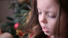 Lilla flickan i röd klänning spelar c-leksaken lager videofilmer