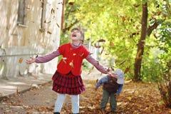 Lilla flickan i röd väst kastar upp sidor Royaltyfri Bild