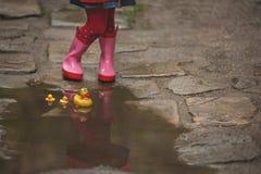 Lilla flickan i regnkängor som spelar med gult gummi, duckar i a Royaltyfri Bild