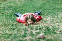 Lilla flickan i rosa färger klår upp att ligga på gräs som ser till kameran royaltyfria bilder