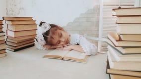Lilla flickan i skolalikformig, avverkar sovande, medan läsa en bok lager videofilmer