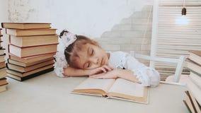Lilla flickan i skolalikformig, avverkar sovande, medan läsa en bok stock video
