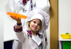 Lilla flickan i vit matlagning beklär att spela med plattan Royaltyfria Foton