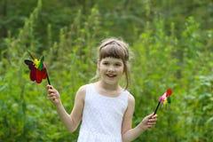 Lilla flickan i vit rymmer två väderkvarnar och leenden Royaltyfria Foton