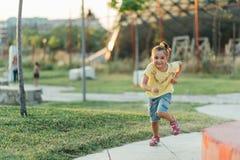 Lilla flickan kör i parkera Royaltyfri Foto