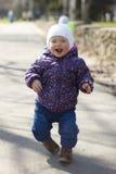 Lilla flickan kör spåret i parkera royaltyfria bilder