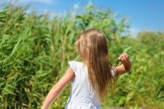 Lilla flickan kastar stenen arkivbild