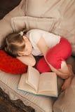 Lilla flickan klädde med filt en sömn, medan läsa en bok arkivfoto