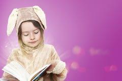 Lilla flickan klädde som en kaninkanin som läser en bok Arkivbilder